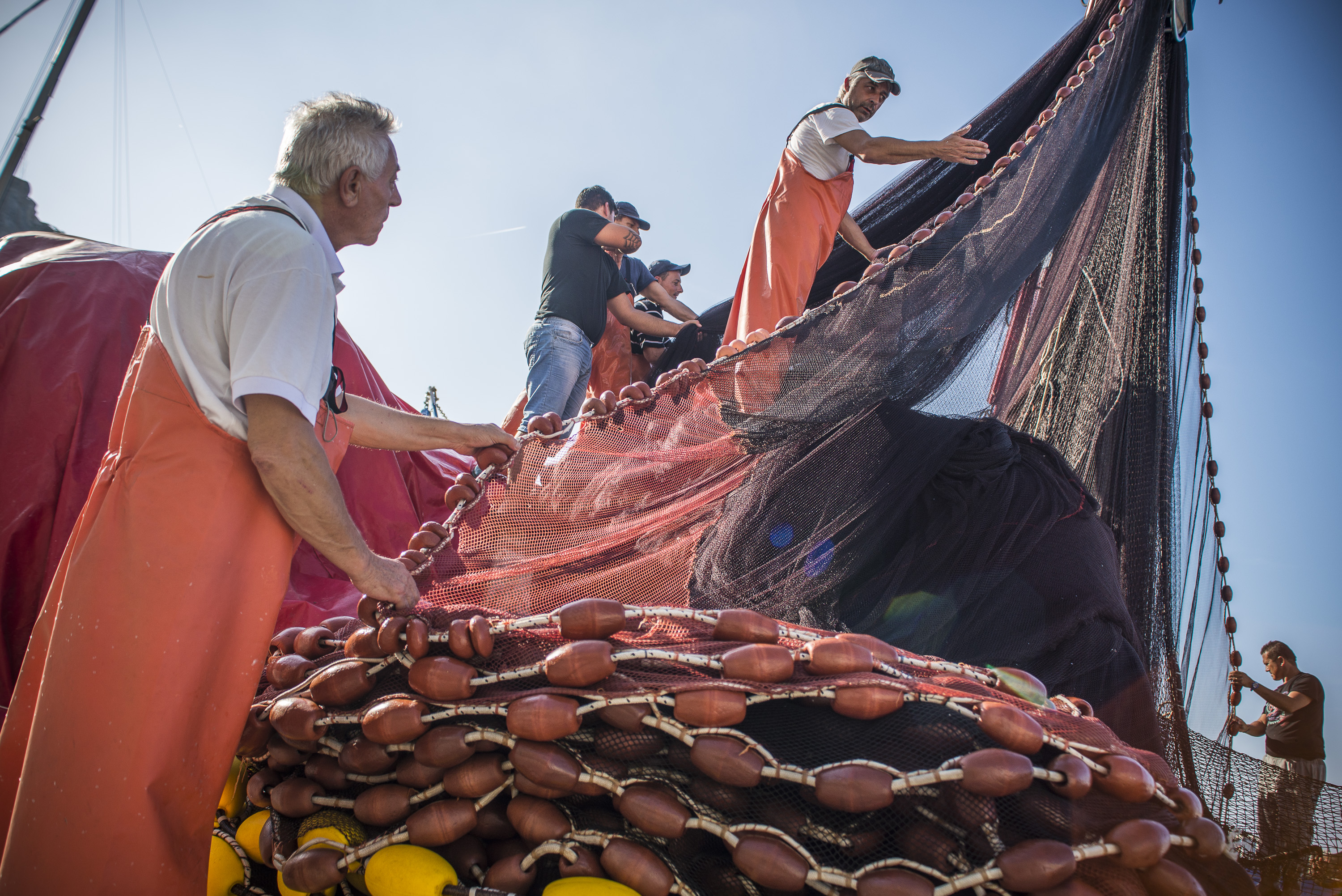 Crew of a local fishing vessel storing fishing nets to dry them and use them in the next spot of fishing in Procida, Italy
