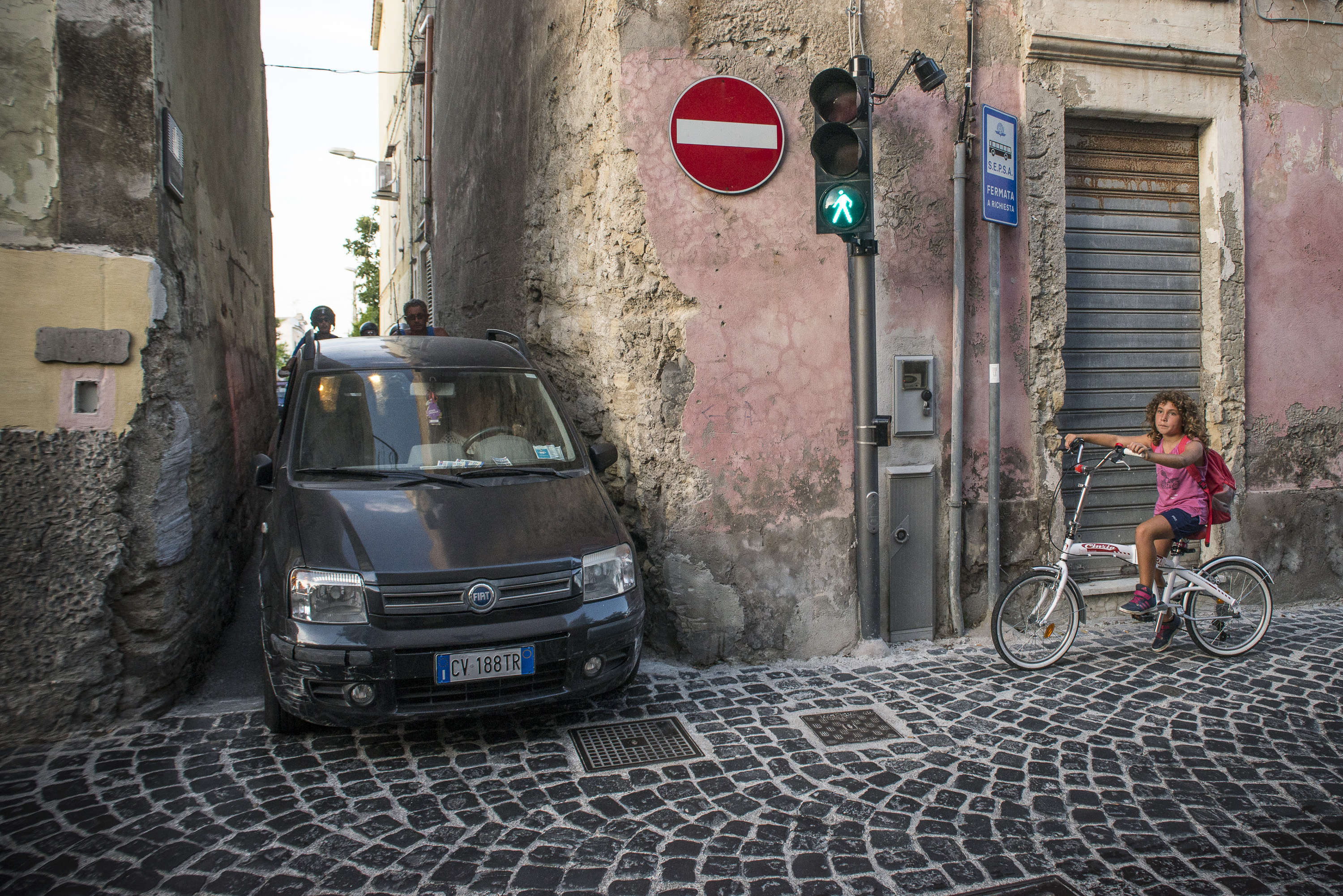 Local car passes through a narrow street that connects the main island road in Procida, Italy