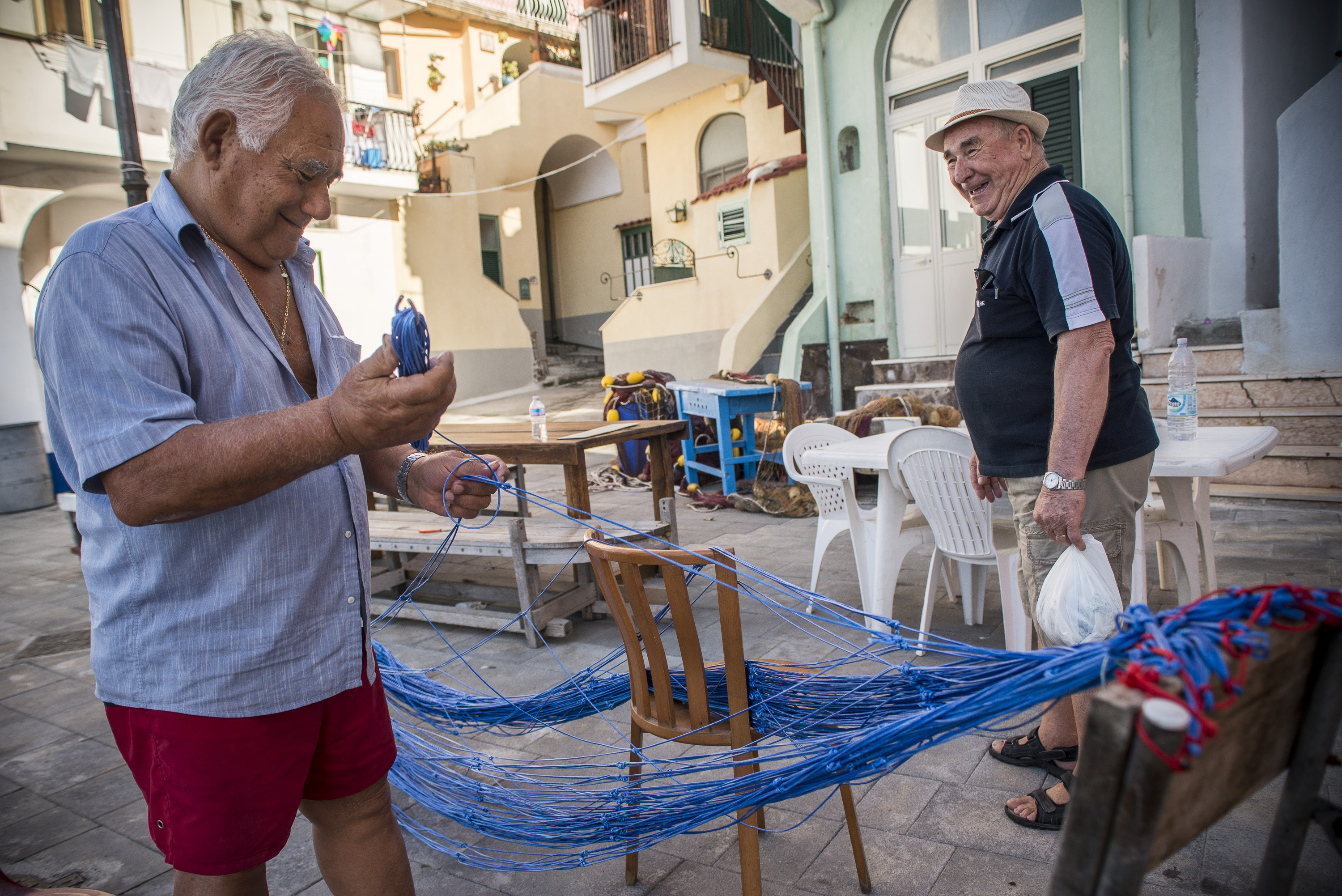 Old retired fisherman repairing fishing nets in Procida, Italy